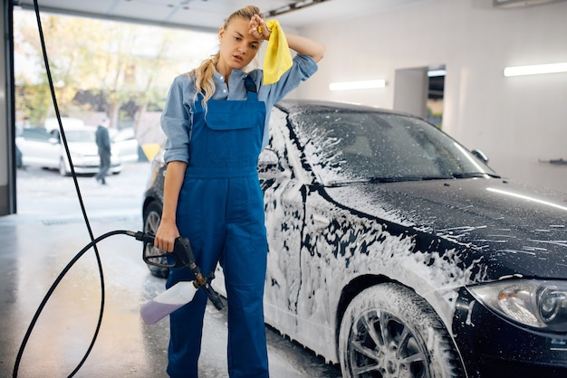 Vermoeide vrouwelijke wasmachine in uniform met schuimpistool in handen, autowassen. vrouw wast auto, autowasstation, autowasbedrijf