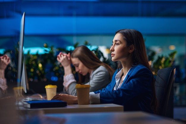 Vermoeide vrouwen zitten aan de tafel in het nachtkantoor. slaperige vrouwelijke zakenvrouwen, donker zakencentruminterieur, moderne werkplek