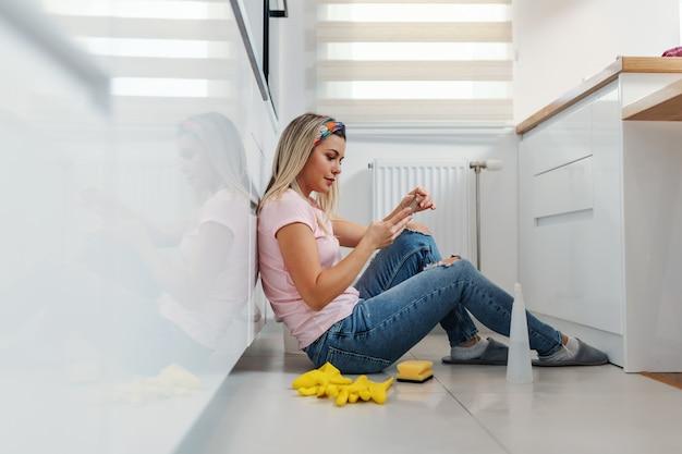 Vermoeide waardige blonde huisvrouw die op de grond in de keuken zit, een pauze neemt en op sociale mediasites hangt.