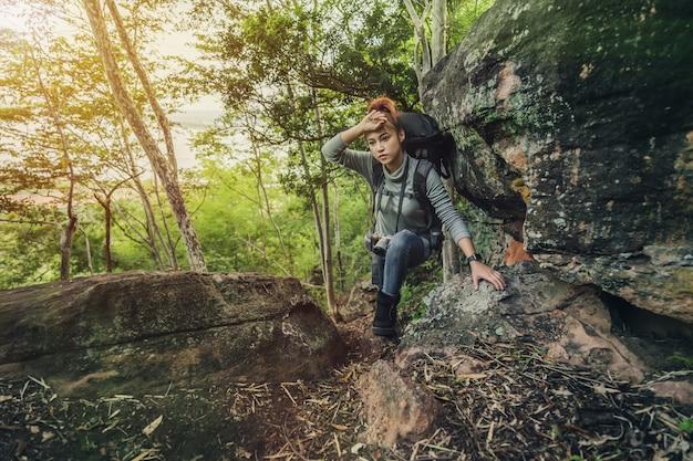 Vermoeide wandelaarvrouw die omhoog in bos beklimmen