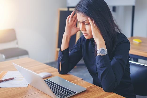 Vermoeide werkende vrouw met hoofdpijn op kantoor.