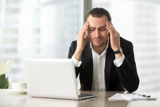 Vermoeide zakenman die aan hoofdpijn lijdt