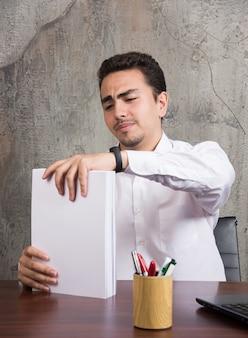 Vermoeide zakenman die bos van documenten bij de balie houdt.