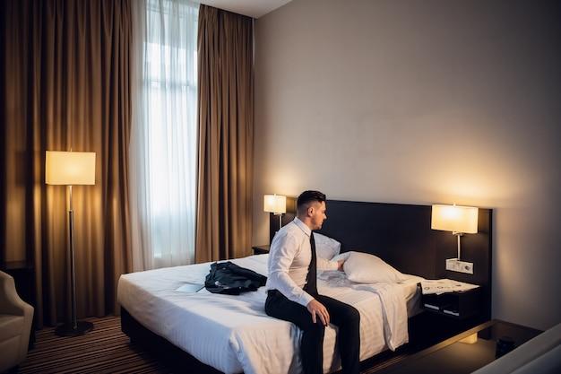 Vermoeide zakenman die voorbereidingen treft om wat rust in zijn hotelruimte te hebben