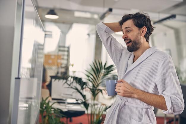 Vermoeide zakenman in witte badjas die naar whiteboard kijkt en geeuwen terwijl hij hete ochtenddrank drinkt op kantoor