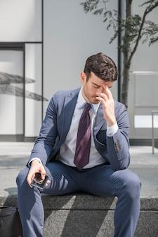 Vermoeide zakenman wrijven voorhoofd