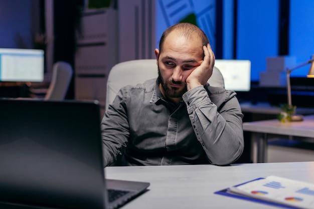 Vermoeide zakenman zit 's avonds achter de computer en werkt op deadline. workaholic-medewerker die in slaap valt omdat hij 's avonds laat alleen op kantoor werkt voor een belangrijk bedrijfsproject.