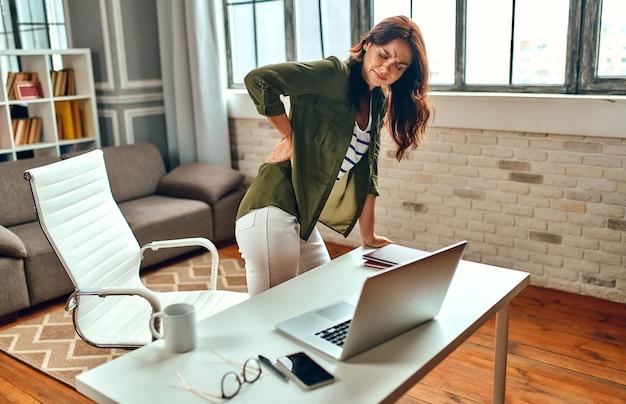 Vermoeide zakenvrouw in stress stond op van haar werkplek en hield haar pijnlijke rug vast. freelance, thuiswerken.