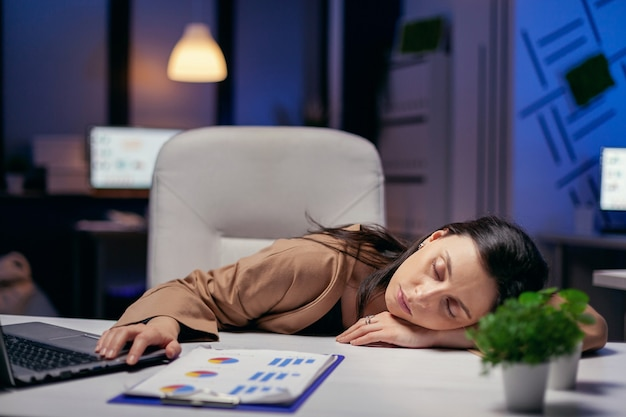 Vermoeide zakenvrouw rustend hoofd op bureau hand in hand op laptop. werknemer valt in slaap terwijl hij 's avonds laat alleen op kantoor werkt voor een belangrijk bedrijfsproject.