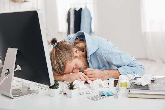 Vermoeide zieke blonde man, die lijdt aan hoofdpijn en hoge temperatuur, hoofd op handen houdt, achter computerscherm zit en gezicht bedekt. zieke kantoormedewerker omringd door pillen en drugs
