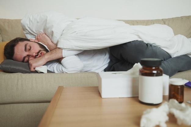 Vermoeide zieke jongeman met zakdoek slapen op de bank onder een deken met zijn hoofd op het kussen terwijl hij thuis blijft voor zelfisolatie