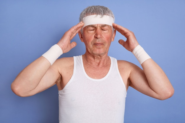 Vermoeide zieke sportman in hoofdband, t-shirt en tailleband, geïsoleerd poseren, handen op het hoofd zetten, ogen gesloten, hoofdpijn hebben.