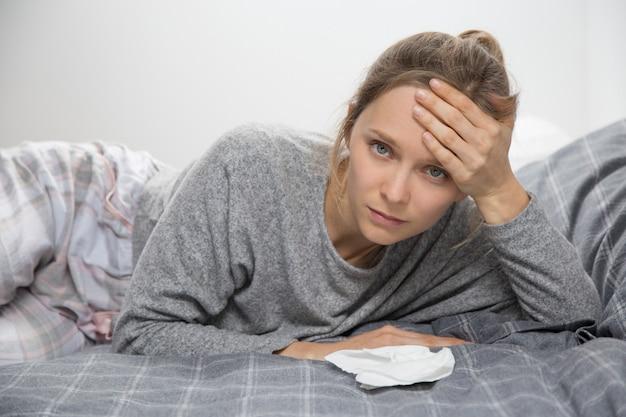 Vermoeide zieke vrouw in de hand van de bedholding op hoofd, die camera bekijkt
