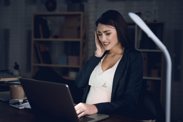 Vermoeide zwangere vrouw met hoofdpijn in office