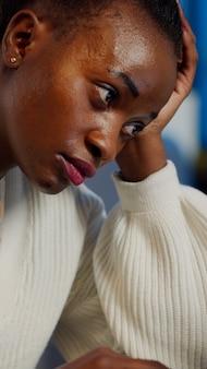 Vermoeide zwarte vrouw die bijna 's avonds laat op een stoel aan het werk is op een laptop in het kantoor van een startbedrijf. drukke werknemer die moderne technologie gebruikt en overuren maakt om het project af te ronden, met inachtneming van de deadline