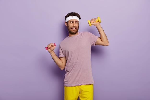 Vermoeidheid en training concept. ontevreden ongeschoren man heft armen op met halters, voelt vermoeidheid van lange training, gekleed in actieve kleding