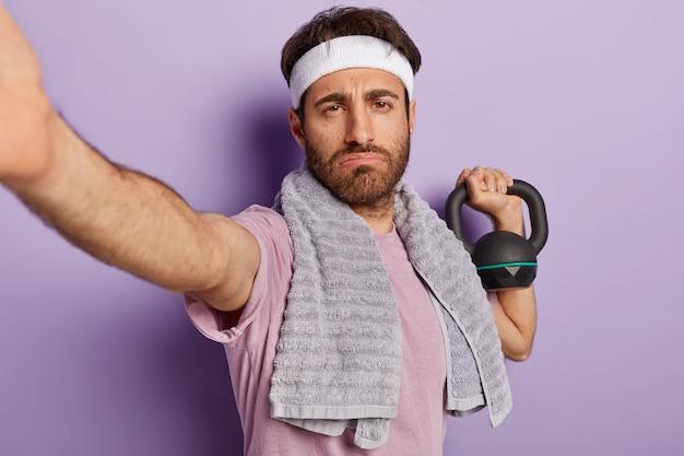 Vermoeidheid ernstige sterke man bodybuilder heeft oefeningen met gewicht, wil perfecte biceps hebben, toont kracht en energie, maakt selfie, gekleed in sportkleding, traint in de sportschool. gewichtheffen