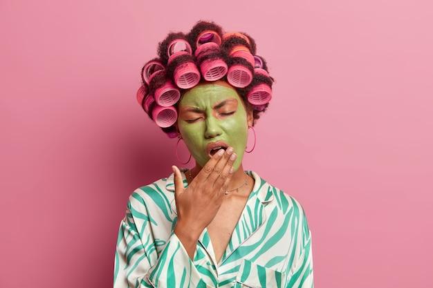Vermoeidheid etnische vrouw gaapt en wil slapen, bedekt de mond met de hand, past een groen avocadomasker toe, draagt haarrollers voor een perfect kapsel, brengt vrije tijd thuis door, geïsoleerd over rooskleurig