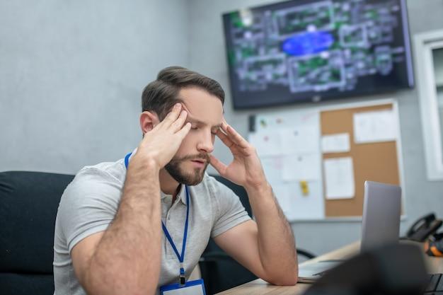 Vermoeidheid. moe jonge volwassen man met gesloten ogen zijn hoofd aan te raken met zijn handen zittend op de werkplek