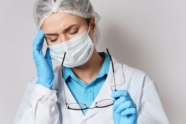 Vermoeidheid of ziekte. jonge vrouwelijke arts met hoofdpijn