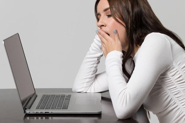 Vermoeidheid op het werk en slaapgebrek. uitgeput vrouw geeuwen, aan tafel zitten en werken op laptop