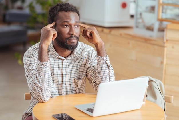 Vermoeidheid verminderen. moe jongeman zittend aan de tafel in de coffeeshop en zijn tempels masseren, uitgeput na langdurig werken op laptop