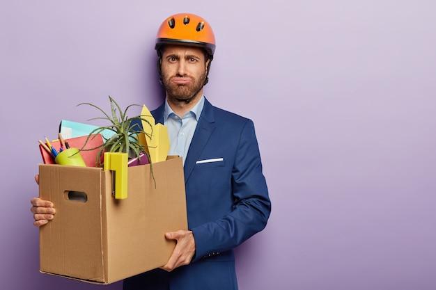 Vermoeidheid zakenman poseren in stijlvol pak en rode helm op kantoor