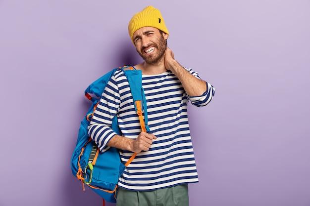 Vermoeidheidstoerist raakt nek aan, voelt stijfheid, draagt vrijetijdskleding, draagt een rugzak, heeft pijnlijke gevoelens, kijkt ongelukkig naar de camera, poseert op een paarse achtergrond. mensen en vermoeiende reis