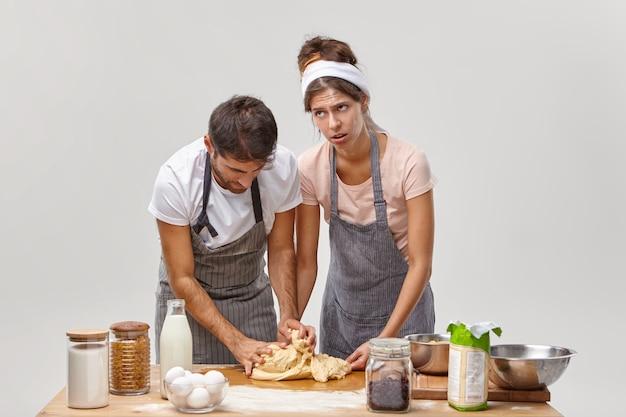 Vermoeidheidsvrouw leert echtgenoot deeg maken, legt uit hoe te kneden en welke ingrediënten toe te voegen, feestelijk diner bereiden, thuis bakken, omringd met noodzakelijke producten op tafel, nieuw recept uitproberen