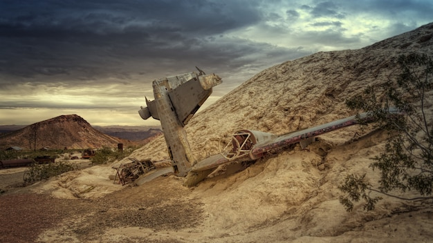 Vernietigd grijs vliegtuig op rots onder grijze luchten