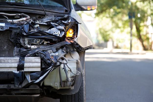 Vernietigde auto in auto-ongeluk verkeersongeval op stadsweg met kopieerruimte. gebroken gebroken auto koplamp, gedeukte kap zonder bumper op grijs auto-ongeluk. auto levens- en ziektekostenverzekering.