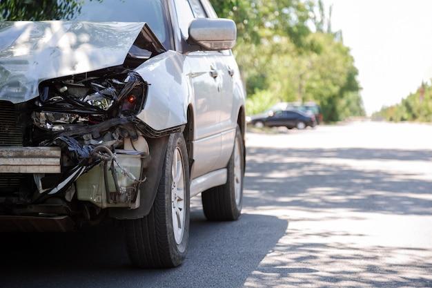 Vernietigde auto in auto-ongeluk verkeersongeval op stadsweg met kopieerruimte op stadsweg. gebroken gebroken autokoplamp, gedeukte motorkap zonder bumper bij auto-ongeluk. auto levens- en ziektekostenverzekering.