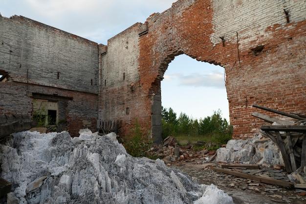 Vernietigde muren van een oud bakstenen gebouw, ruïnes.