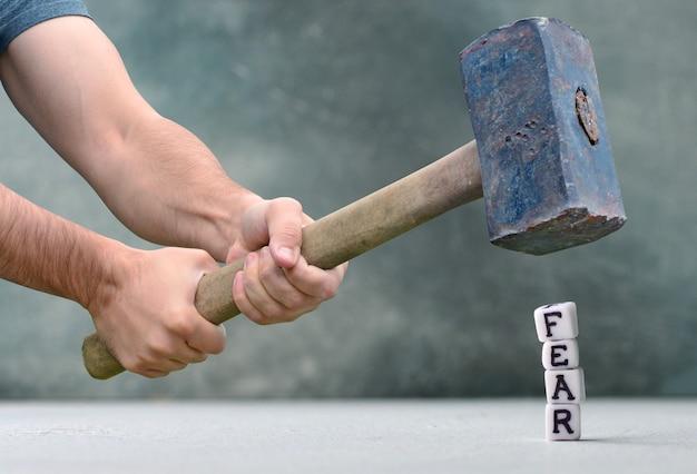 Vernietiging van angsten concept met letters en grote hamer.