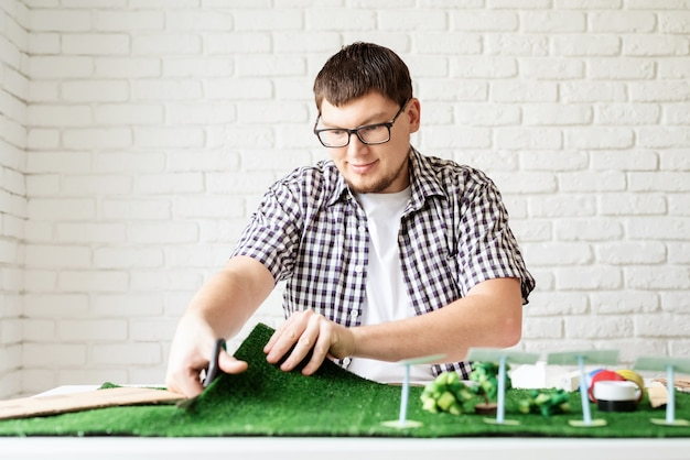 Vernieuwbare energieconcept. ambachten en wetenschappelijke projecten. jonge man die project dummy voor hernieuwbare energie maakt