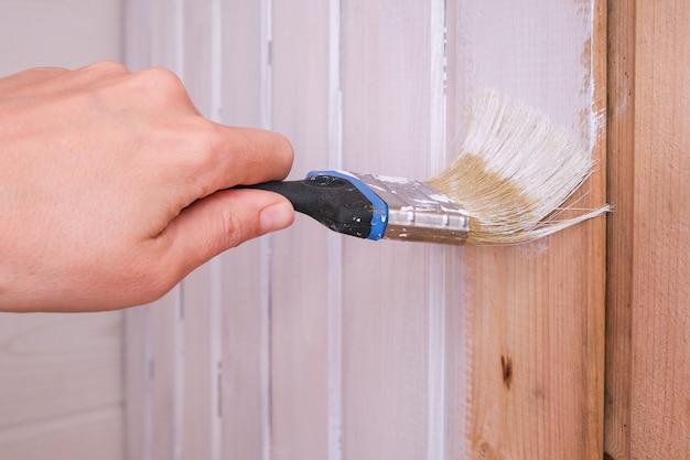 Vernieuwing van houten huizen, het met de hand opnieuw schilderen van een plankenmuur in een witte kleur met een penseel en latex of anryl interieurverf, ecologische en ademende materialen.