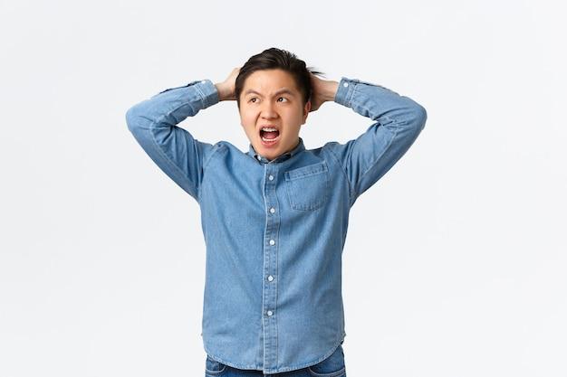 Verontruste en bezorgde aziatische man die in paniek raakt, grote problemen heeft, geconfronteerd wordt met een vreselijke situatie, handen op het hoofd houdt besluiteloos en gefrustreerd, wegkijkend, weet niet wat doen, witte achtergrond