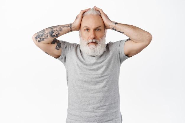 Verontruste en bezorgde oude man met tatoeages, handen op het hoofd en verward kijken, in paniek raken of zich nerveus voelen over een ongeluk, gealarmeerd en besluiteloos tegen de witte muur staan