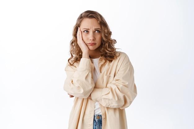 Verontruste jonge vrouw houdt de hand op het gezicht, kijkt bezorgd en verdrietig opzij, staart naar de kopieerruimte, staande tegen een witte muur