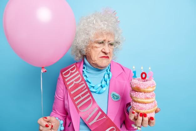 Verontruste, ongelukkige oudere vrouw die boos is over ouder worden, houdt een stapel geglazuurde donuts vast en viert verjaardag alleen voelt zich eenzaam gekleed in modieuze kleding poses met ballon binnen