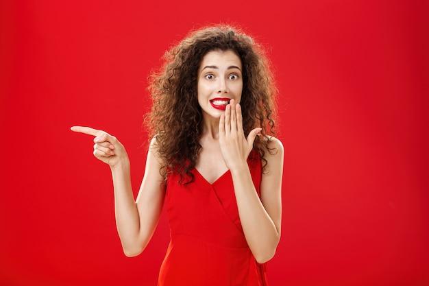 Verontruste schattige en tedere dwaze vrouw met krullend kapsel in rode stijlvolle avondjurk die oeps zegt en glimlacht met een schuldige blik die mond bedekt met palm terwijl ze naar de achtergrond van de studio wijst.