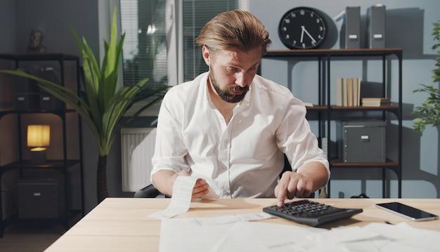 Verontruste zakenman zittend aan tafel met rekeningen in de ene hand en het controleren van nummers op de rekenmachine