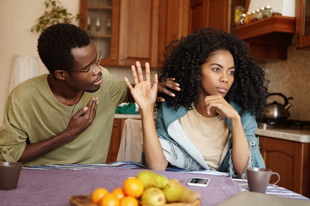 Verontschuldigend afro-amerikaanse mannelijke hand houden op zijn borst proberen gekke vrouw te overtuigen in zijn trouw. zwarte vrouw negeert de excuses van haar ontrouwe echtgenoot. liefde en relatieproblemen