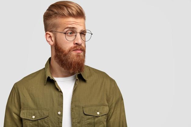 Verontwaardigd gember mannetje kijkt opzij met een verbaasde, doordachte uitdrukking, trekt wenkbrauwen op, draagt een bril, draagt modieuze kleding