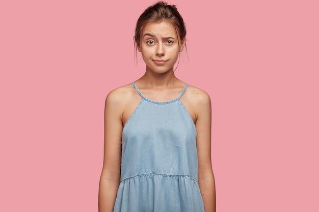 Verontwaardigd jong meisje trekt wenkbrauwen op van verbijstering, heeft onverwachte reactie
