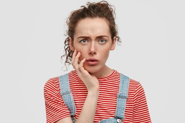 Verontwaardigd jonge vrouw met sproeten poseren tegen de witte muur