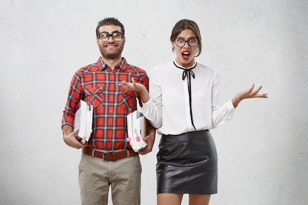 Verontwaardigd vrouwelijk model gebaart van ontevredenheid, beseft hoeveel stof ze moet weten voor het examen