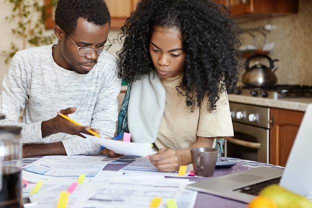 Verontwaardigde afrikaanse echtgenoot gebaart met potlood en verwijt zijn vrouw dat ze een fout heeft gemaakt bij het berekenen van rekeningen