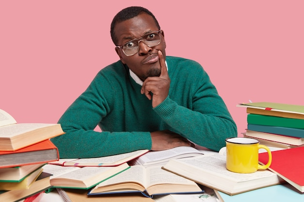 Verontwaardigde afro-amerikaanse man kijkt ongenoegen, heeft een donkere huid, draagt een groene trui, houdt de hand bij de mond, denkt na over toekomstige plannen