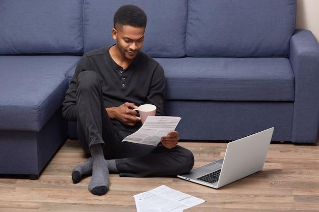 Verontwaardigde afro-amerikaanse ondernemer kijkt met ontevreden uitdrukking naar papieren documenten en draagt een wegwerpbeker koffie